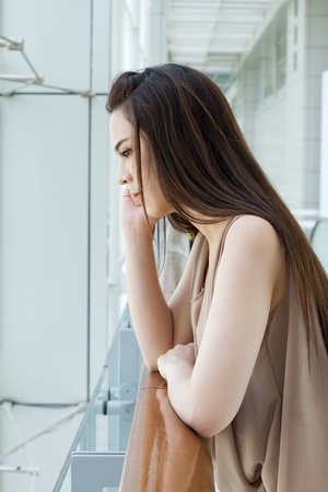 unhappiness: thinking woman with mild stress, worry and unhappiness