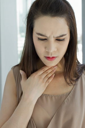 sore throat: sick woman with throat problem  Stock Photo