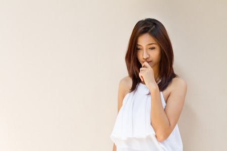 thinking woman, facing downward on plain warm tone for text space Stock Photo