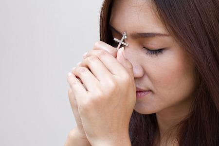 manos orando: mujer que ora con la cruz santa