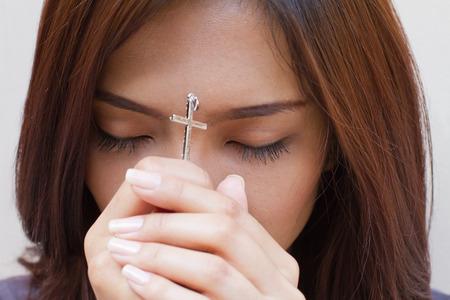 personas orando: mujer que ora con la cruz santa, cerr� los ojos Foto de archivo