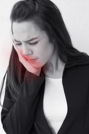 dolor de muelas: mujer sufre de dolor de muelas, con acento de alerta roja de peligro Foto de archivo