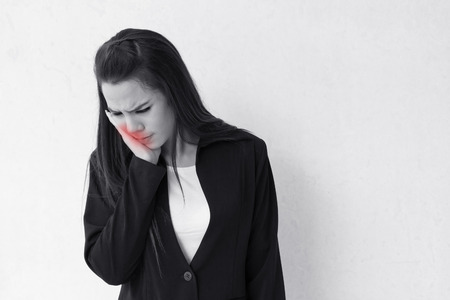 woman suffers from toothache, with red alert danger accent Stock Photo