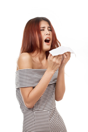 sick woman sneezing due to flu, cold, allergy, white isolated background photo