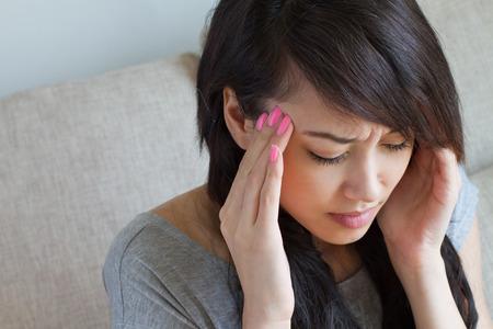 vrouw met hoofdpijn, migraine, stress, slapeloosheid, kater, Aziatische Kaukasische binnenscène Stockfoto