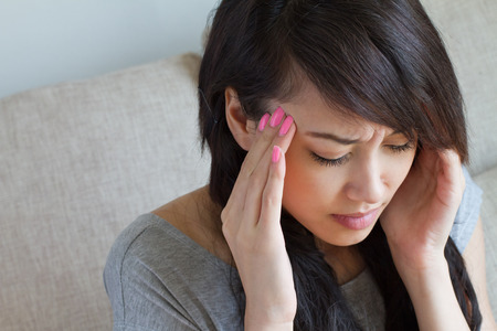 headache pain: woman with headache, migraine, stress, insomnia, hangover, asian caucasian indoor scene Stock Photo