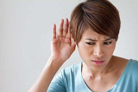 listening to people: woman suffers from hearing impairment, hard of hearing, hearing loss, acoustic or ear problem, deafness with text space Stock Photo