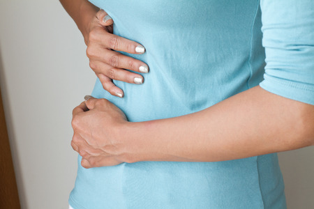 chronic pain: menstruation pain or stomach ache, hand holding belly closeup