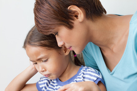 childs problem with caring mother; listening to her daughters problem : head and shoulder shot Stock Photo