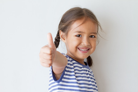 girl giving thumb up hand sign photo