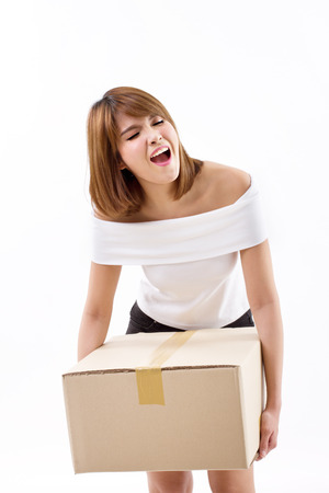 unhappy woman carrying heavy box with pain photo