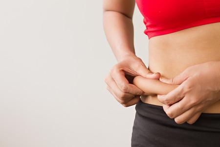mujer celulitis: La mano de la mujer que sostiene la excesiva grasa del vientre
