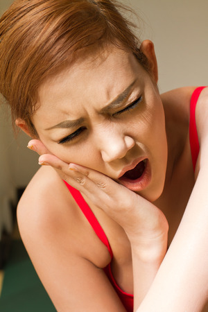 sensitivity: woman suffering from jaw pain, toothache, tooth sensitivity