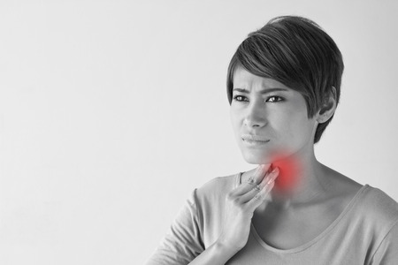 painful: sick woman with sore throat. Stock Photo