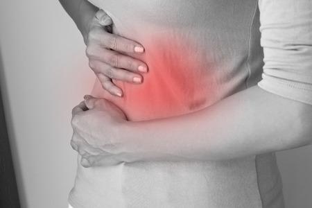 menstruacion: dolor de la menstruaci�n o dolor de est�mago, la mano que sostiene el vientre de cerca Foto de archivo