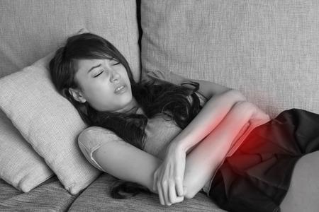 menstruacion: dolor de la menstruación, período calambres, dolor de estómago, problema digestivo de la mujer en escena de interior Foto de archivo