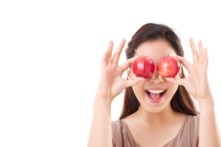 healthy and playful woman covering her eyes with two red apples, brown dress for summer and spring season photo