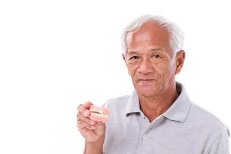 old senior man with hand holding denture Stock Photo