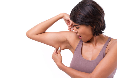 mujer celulitis: infeliz mujer con la mano sosteniendo la grasa del brazo excesivo, aislado en fondo blanco