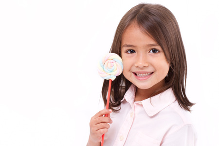 playful cute little girl posing with sweet pastel color marshmallow photo