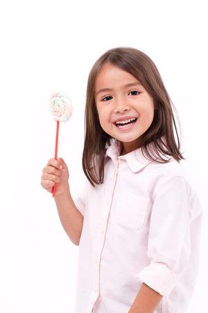 happy, smiling cute little girl eating marshmallow sweet candy Foto de archivo