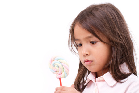 reluctant: little girl looking at sweet marshmallow candy