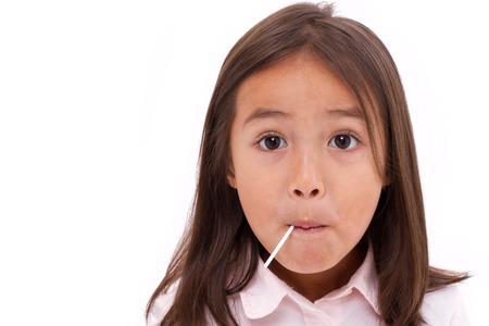 mignonne petite fille: Mignon petite fille mangeant bonbon sucré Banque d'images