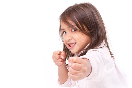 Little girl assuming stance, practicing martial arts, self-defense, kungfu, karate, boxing