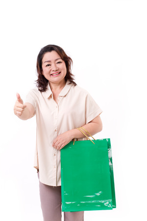 thumbup: thumb up gesture from happy middle aged asian woman with shopping bag Stock Photo