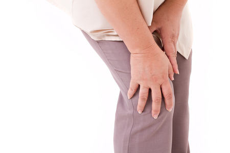 middle joint: middle aged woman suffering from knee pain, joint injury or arthritis, hand holding knee