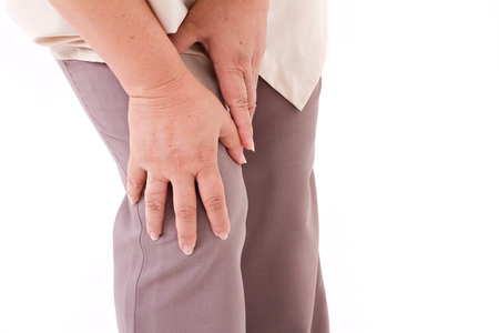 human leg: middle aged woman suffering from knee pain, joint injury or arthritis, hand holding knee