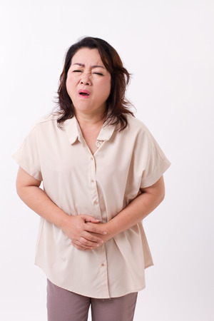 indigestion: middle aged woman suffering from stomach ache, belly pain, menstuation, menopause, indigestion problem