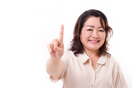 woman pointing: happy, confident middle aged woman pointing up one finger, number 1 hand sign gesture Stock Photo