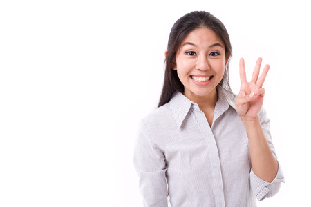pointing finger up: happy woman showing 3 fingers gesture Stock Photo