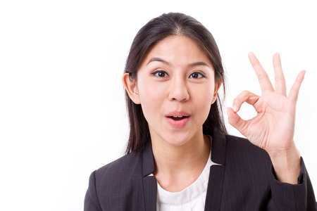 happy, smiling, successful business woman showing ok hand gesture
