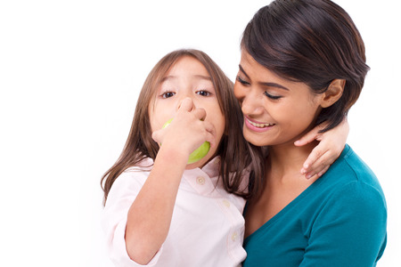 race relations: happy family, mother and daughter with raw organic green apple, concept of healthy food
