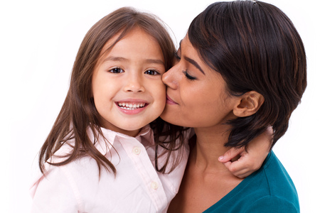 race relations: mother kissing her daughters cheek, concept of family love Stock Photo