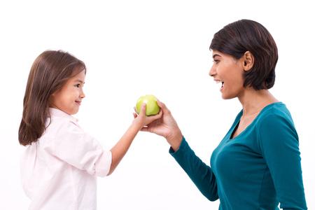 dieta sana: familia feliz, madre e hija con prima de manzana verde orgánico, el concepto de la comida sana Foto de archivo