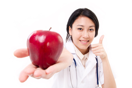 suggesting: smiling female doctor suggesting red apple, giving thumb up gesture