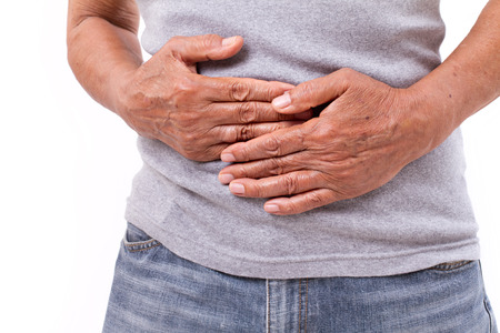 acid reflux: hand of old man holding stomach suffering from pain, diarrhea, indigestive problem Stock Photo