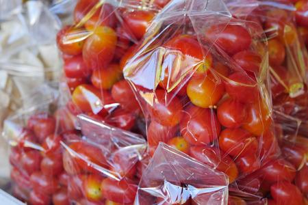 basura organica: tomate cherry embalado en una bolsa de plástico Foto de archivo