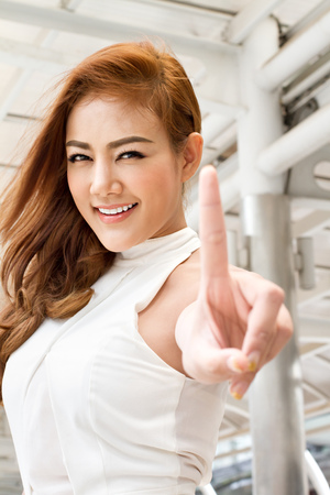 pointing finger up: confident woman pointing one finger up Stock Photo