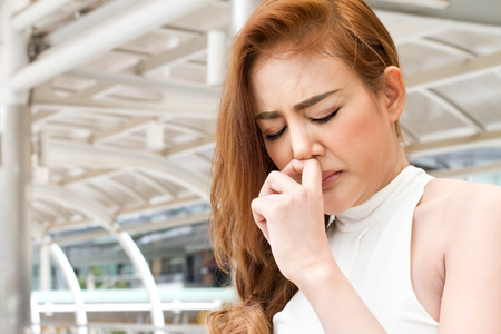 nose drops: sick woman suffering from runny nose