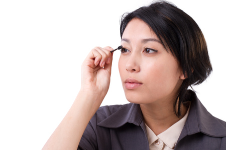 making up: business womans grooming, making up, looking up to blank space Stock Photo