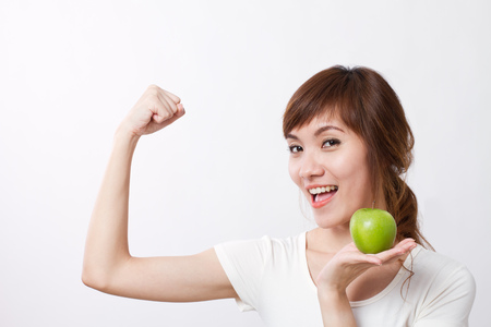 healthy looking: healthy, strong asian woman with green apple, looking at you Stock Photo