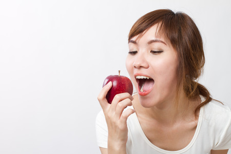 healthy asian woman looking up while biting, eating red apple