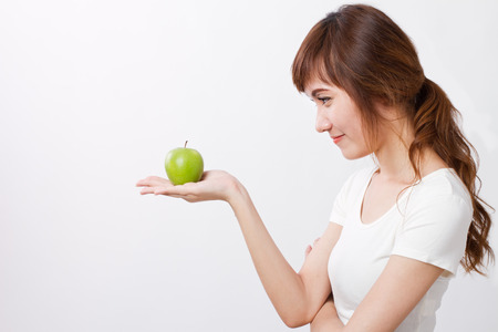 healthy looking: healthy asian woman looking at green apple
