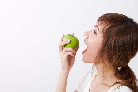 healthy looking: healthy asian woman looking up while biting, eating green apple