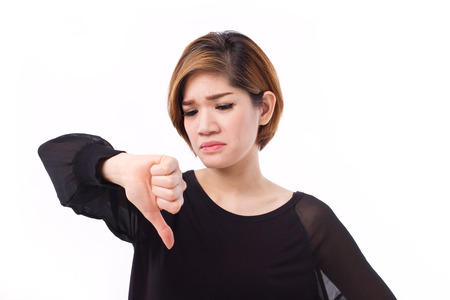 displeased: displeased, frustrated, unhappy woman giving thumb down gesture, studio isolated of Asian Chinese-Thai woman model. Stock Photo