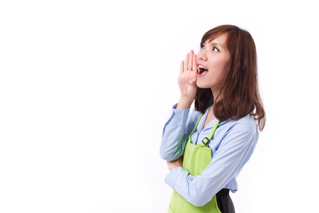 announcing: happy, smiling woman with apron shouting, speaking, communicating, announcing, studio isolated Stock Photo